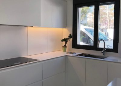 Mobiliario de cocina lacado en blanco. Puertas coplanares en frente de bancada 12