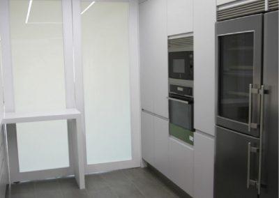 Mobiliario de cocina lacado en blanco, con uñero integrado y puertas vidrieras pivotantes casino-09