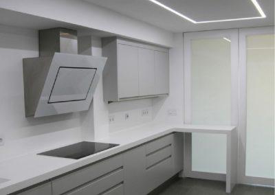 Mobiliario de cocina lacado en blanco, con uñero integrado y puertas vidrieras pivotantes casino-11