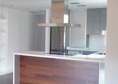 Mobiliario de cocina laminado gris. Isla con frente de tarima de madera.